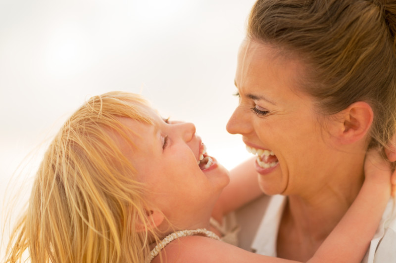 Portrait of smiling mother and baby girl hugging on the beach in the evening